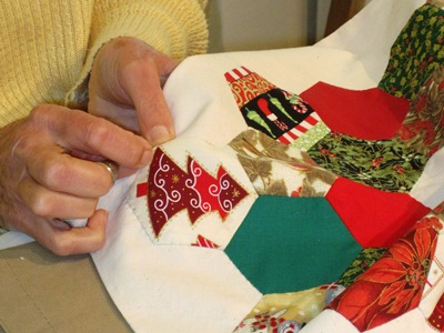 Hands sewing a quilt